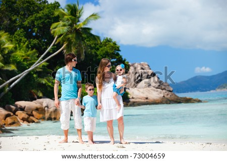Portrait of happy young family with two kids on tropical vacation - stock photo