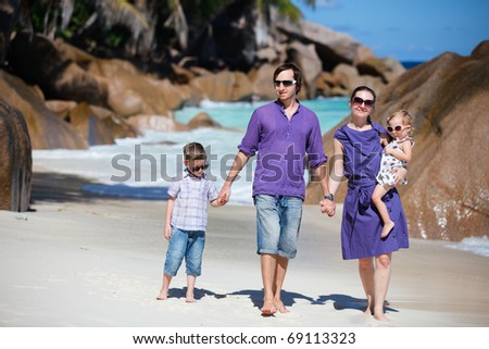 Portrait of happy young family with two kids walking along tropical beach - stock photo