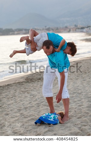 portrait of happy young father with little daughter and son, outdoors near sea - stock photo