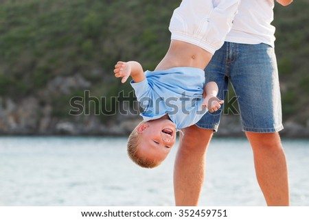 portrait of happy young father with little son, outdoors near sea - stock photo