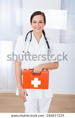 Portrait of happy young female doctor holding first aid box in hospital - stock photo