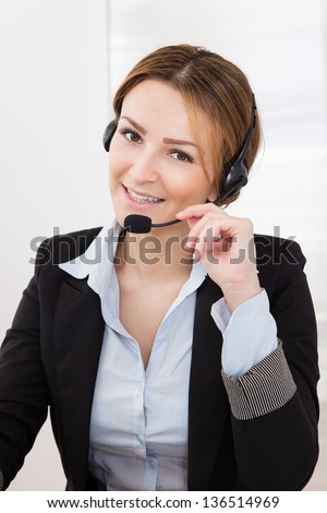 Portrait Of Happy Young Female Operator With Headphones