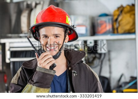 Portrait of happy young fireman using walkie talkie at fire station - stock photo