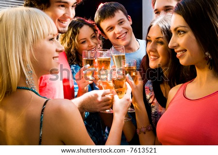 Portrait of happy young friends touching the glasses with each other - stock photo