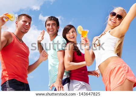 Portrait of happy young friends with cocktails having beach party - stock photo