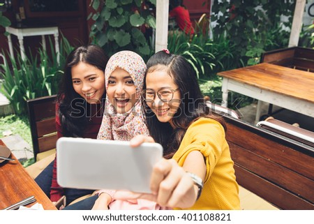 portrait of happy young girl friend taking selfie together in cafe - stock photo