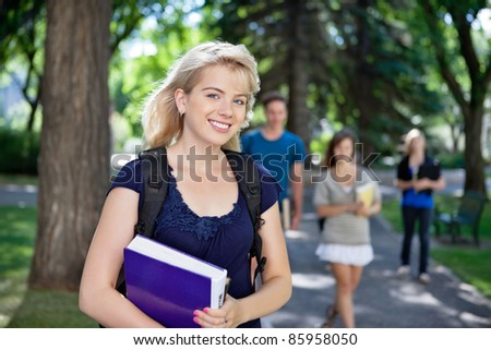 Portrait of happy young girl smiling while her classmates walking in background - stock photo