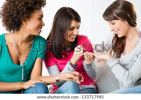 Portrait Of Happy Young Girls Applying Nail Paint While Sitting On Couch - stock photo