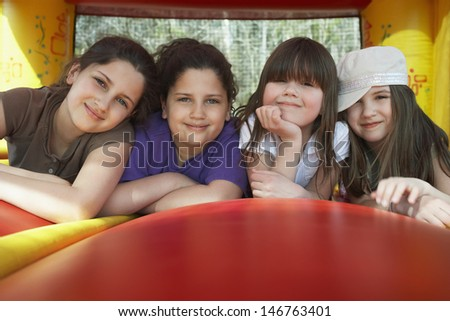 Portrait of happy young girls relaxing in bouncy castle