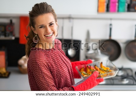 Portrait of happy young housewife holding baked pumpkin - stock photo