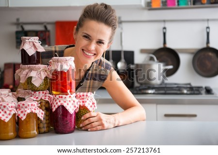 Portrait of happy young housewife looking out from jars with homemade fruits jam and pickled vegetables - stock photo