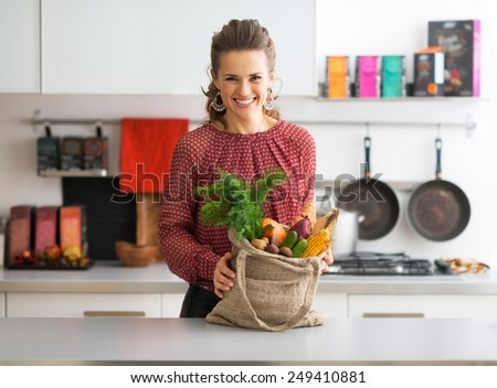 Portrait of happy young housewife with local market purchases in kitchen - stock photo