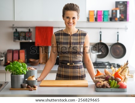 Portrait of happy young housewife with vegetables in kitchen - stock photo