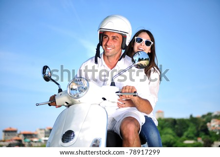 Portrait of happy young love couple on scooter enjoying themselves in a park at summer time - stock photo