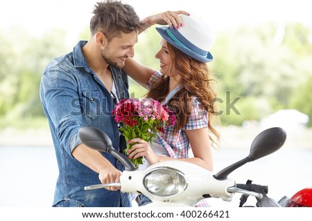 Portrait of happy young love couple on scooter in a park at summer time