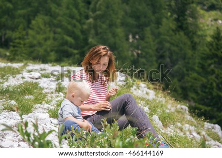 Portrait of happy young loving mother and her baby outdoors spending time. Beautiful woman with a child on hands standing in the forest and mountains. Travel explore family concept