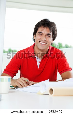Portrait of happy young male architect working on blueprints at desk - stock photo