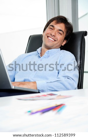 Portrait of happy young male interior designer using laptop - stock photo