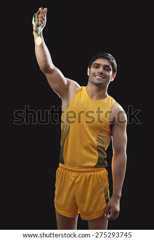 Portrait of happy young male runner in sportswear holding gold medal over black background - stock photo
