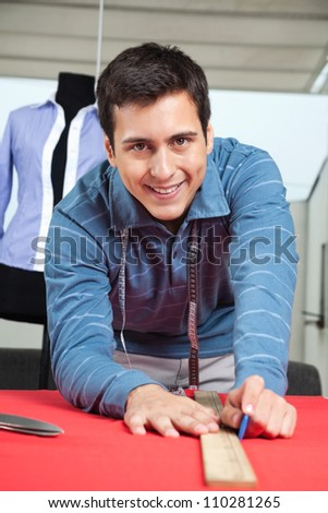 Portrait of happy young male tailor drawing line on a red fabric with chalk - stock photo