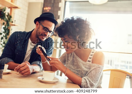 Portrait of happy young man and woman sitting together at a restaurant and looking at a mobile phone. Young friends looking at smart phone while sitting in cafe - stock photo