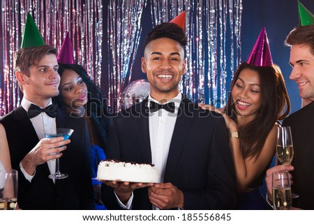 Portrait of happy young man celebrating birthday with friends in nightclub