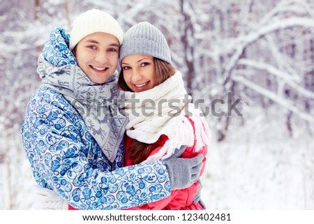 Portrait of happy young man embracing his girlfriend in winter park - stock photo