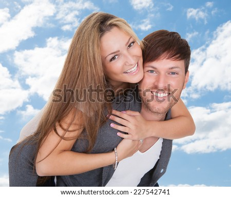 Portrait of happy young man giving piggyback ride to girlfriend against sky - stock photo
