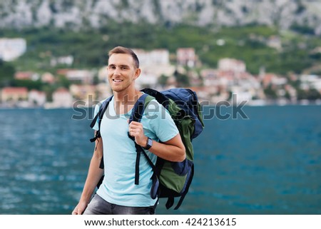 Portrait of happy young man hiking along shore. - stock photo