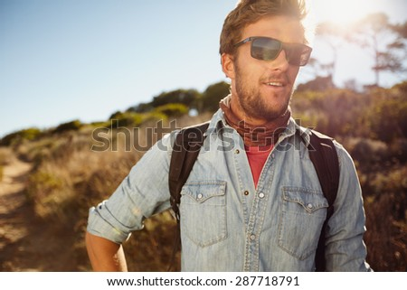 Portrait of happy young man hiking in countryside. Caucasian male model with backpack hiking on sunny day. Summer vacation in countryside.