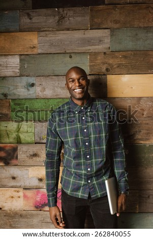 Portrait of happy young man holding a laptop looking at camera smiling while standing in office against a wooden wall. African american male model. - stock photo