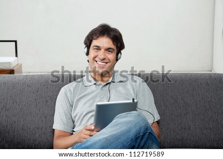 Portrait of happy young man in casual wear listening music on tablet PC - stock photo