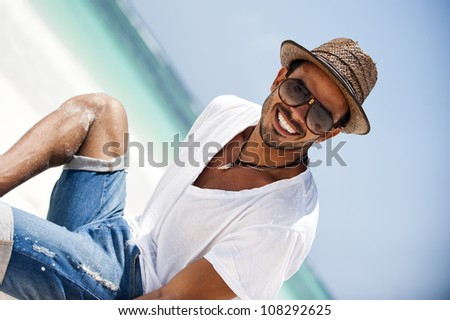 Portrait of happy young man on a tropical beach - stock photo