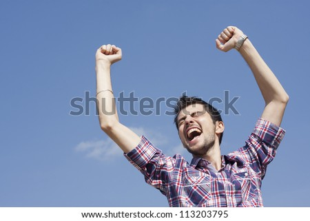 Portrait of happy young man raising his hands with cloudy sky above him - stock photo