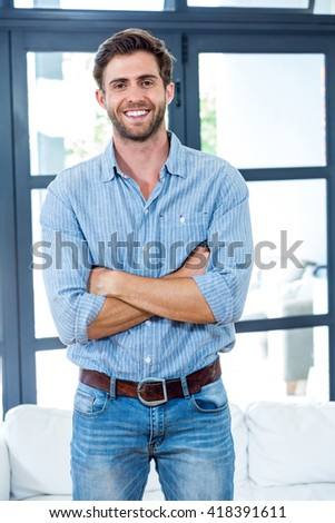 Portrait of happy young man with arms crossed while standing at home - stock photo