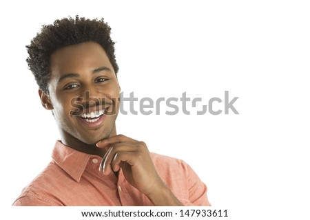 Portrait of happy young man with hand on chin against white background - stock photo