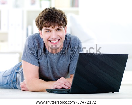 Portrait of happy young  man with laptop - indoors - stock photo
