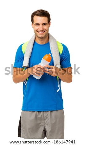 Portrait of happy young man with towel and water bottle standing isolated over white background. Vertical shot. - stock photo