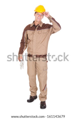 Portrait Of Happy Young Mechanic Wearing Yellow Hardhat On White Background - stock photo
