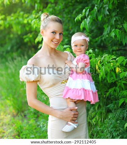 Portrait of happy young mother and baby daughter wearing a dress together having fun in summer day - stock photo