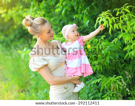 Portrait of happy young mother and baby daughter wearing a dress together in summer day - stock photo