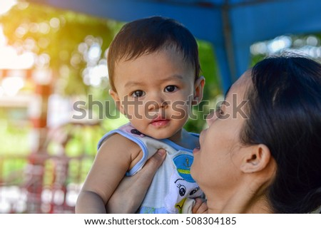 Portrait of happy young mother and her baby outdoor