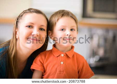Portrait of happy young mother and son baking together. Flour on theirs faces. - stock photo
