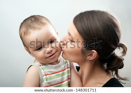 portrait of happy young mother and toddler on white and grey background - stock photo