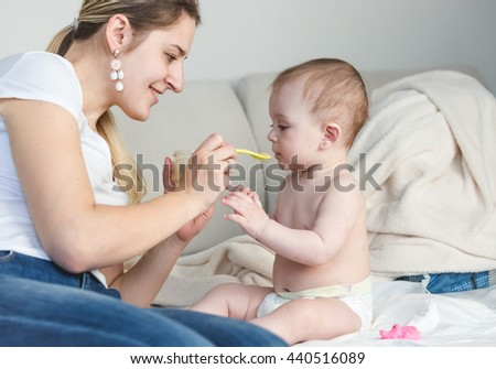 Portrait of happy young mother feeding her baby on bed with a spoon - stock photo