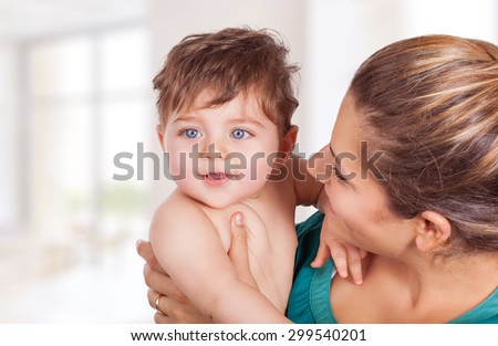 Portrait of happy young mother holding on hands cute little son and looking on him with great love, with pleasure spending time at home, enjoying motherhood - stock photo