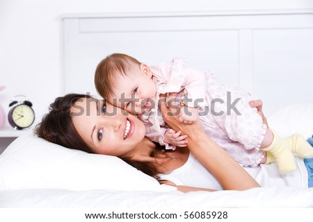 Portrait of happy young mother lying with her baby on the bed at home - stock photo