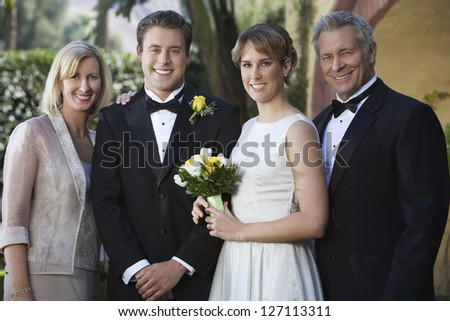 Portrait of happy young newly married couple standing with parents - stock photo