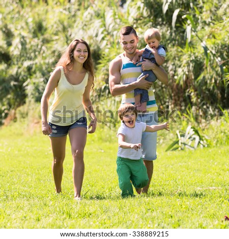 Portrait of happy young parents with two children in summer park. Focus on girl