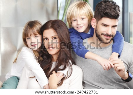 Portrait of happy young parents with two kids sitting at sofa. - stock photo